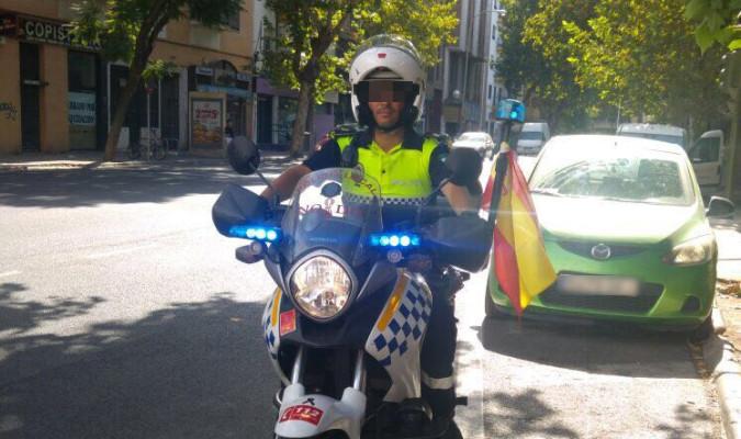 Un agente de la Policía Local de Sevilla patrulla con la bandera de España.