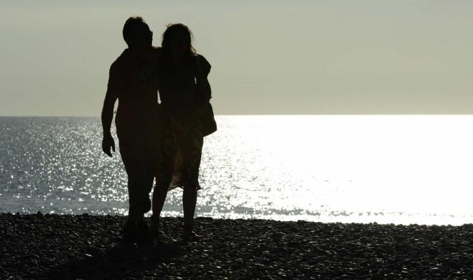 Una pareja camina por la playa de Normandia (Francia). / Efe