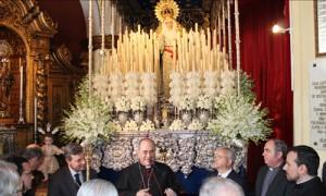 El arzobispo de Sevilla, monseñor Juan José Asenjo, dirige unas palabras a los hermanos de Las Aguas junto al paso de palio de la Virgen de Guadalupe.
