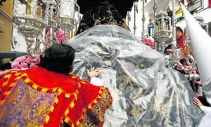 Un hermano de la Cena cubre el manto de la Virgen del Subterráneo el Domingo de Ramos.