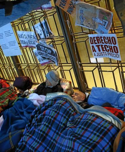 Afectados por desahucios duermen  a las puertas de un banco. / JUAN MEDINA (REUTERS)