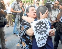 Una madre se abraza a su hijo cuando van a ser desahuciados en el barrio de la Macarena, en Sevilla