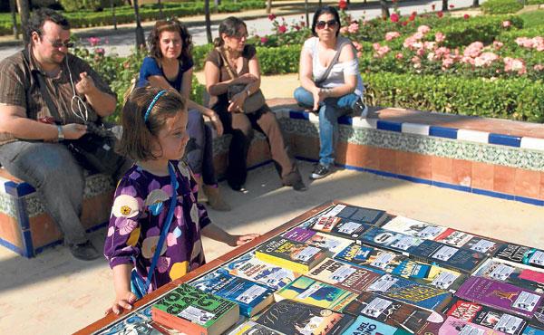 Varios lectores participan de un acto de 'book crossing' ayer en el sevillano Parque de María Luisa. / Foto: Manu R. R.