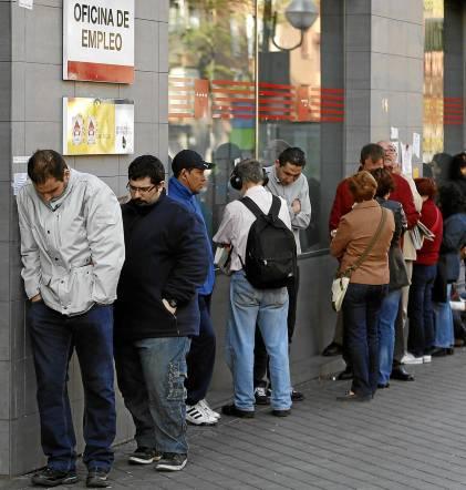 Una cola de personas espera ante las oficinas de demanda de empleo en Sevilla.