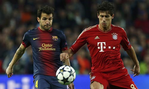 Bayern Munich's Martinez is challenged by Barcelona's Fabregas during their Champions League semi-final second leg soccer match at Camp Nou stadium in Barcelona