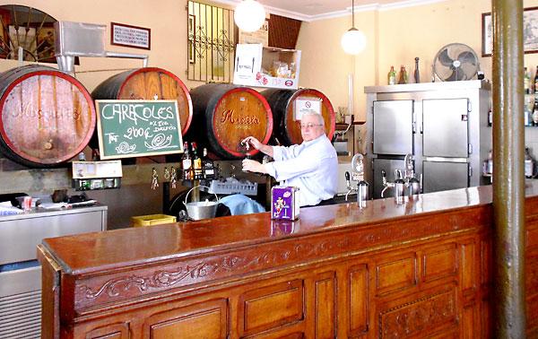 Agustín Sánchez sirve una copa de mistela tras el mostrador de madera del local.
