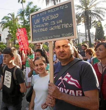 Los manifestantes muestran pancartas en pizarrines al pasar frente a la sede del PP-A. / J. M. Paisano (Atese)