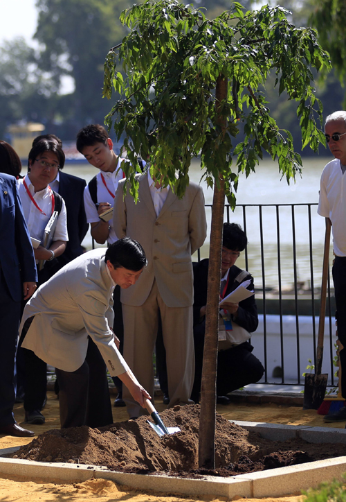 Japan's Crown Prince Naruhito takes part in the planting of a cherry tree during his visit to Coria del Rio
