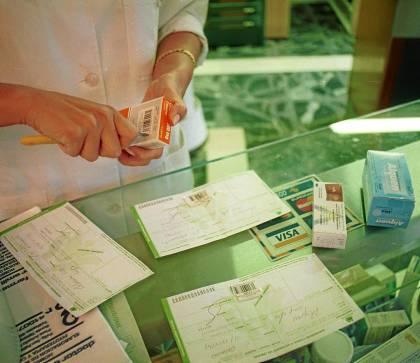 Una farmacéutica dispensa un medicamento con una receta del paciente. / Paco Sánchez