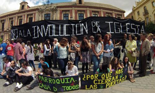 Miembros de la pastoral de Mairena portan una pancarta de protesta ante el Arzobispado de Sevilla.