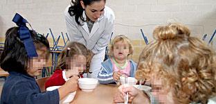 Niños de una escuela infantil comen el desayuno que les sirve una de las maestras.