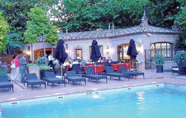 El restaurante está en el jardín del hotel junto a la piscina.