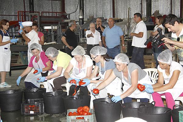 Voluntarios de Los Palacios pelando los tomates de la fritá.