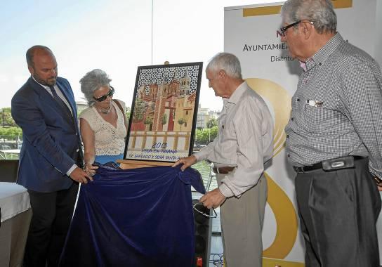 El delegado Francisco Pérez, la pregonera Rosa Díaz, el cartelista Juan Romero y Ángel Vela descubren el cartel de la Velá de Triana. / J.J. Espino (ATESE)