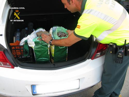 Un agente muestra la droga encontrada en el maletero del vehículo. Foto: Guardia Civil.
