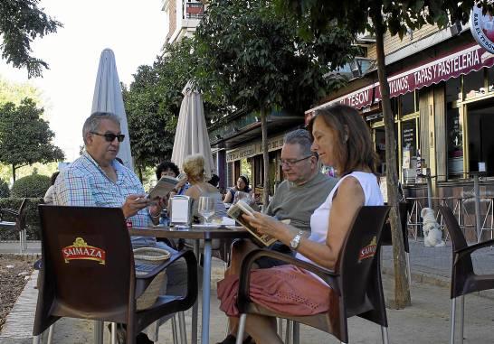Vecinos de Pío XII leyendo un libro en la terraza del bar Tesón.