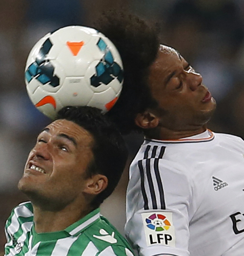Real Madrid's Marcelo and Real Betis' Molina head the ball during  their Spanish first division soccer match in Madrid