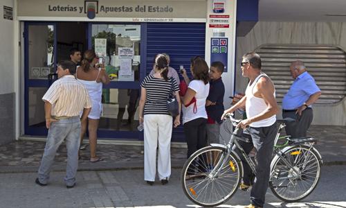 Varios curiosos ante la administración de lotería 108, en la calle Pedro Romero del barrio sevillano de San Pablo, donde se había validado el boleto de la Lotería Primitiva que batió ayer un record con un único premio de más de 67,1 millones de euros. / EFE
