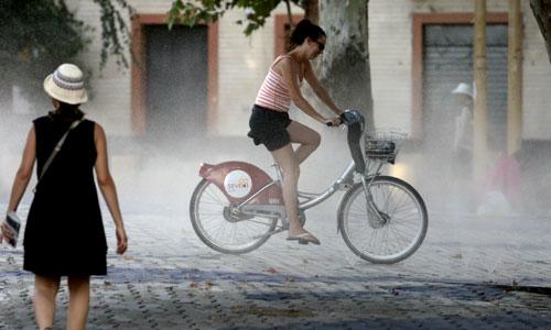 Una chica pasea en bicicleta por la Alameda de Hércules. / El Correo