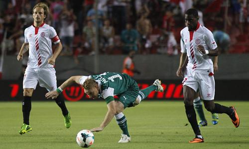 El jugador del Slask Wroclaw, Mila (c ), es derribado por el jugador del Sevilla FC, Kondogbia (d), durante el partido de la ronda previa a la fase de grupos de la Liga Europa disputado en el estadio Ramón Sánchez Pizjuán. / EFE
