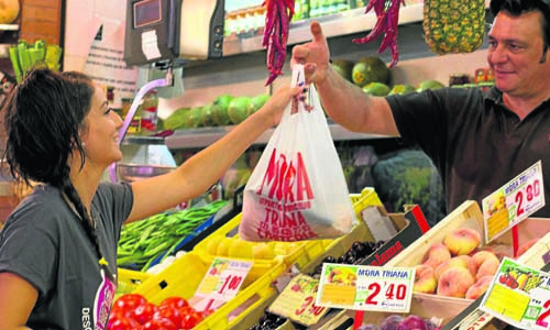 Rocío recibe un descuento en el puesto de Pepe Mora del mercado de Triana por ser desempleada. / Manuel R.R. (ATESE)