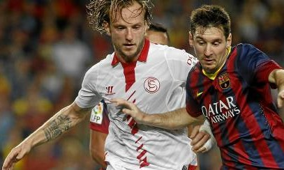 Rakitic, disputando un balón con Messi.