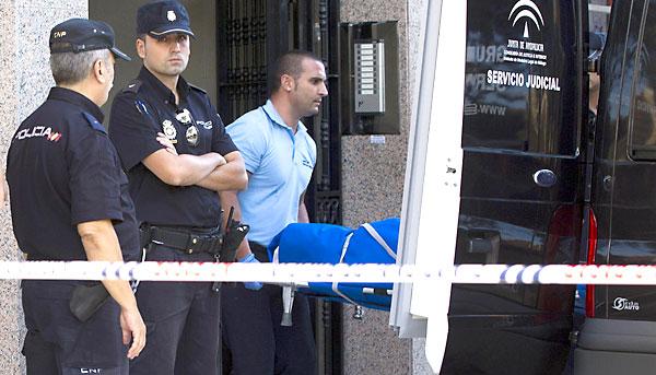 Efectivos de los servicios funerarios trasladan el cuerpo de una de las dos víctimas. / EFE