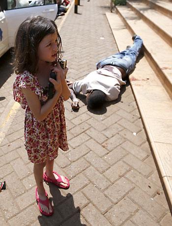 Una niña junto a un cuerpo en las afueras del centro. / REUTERS