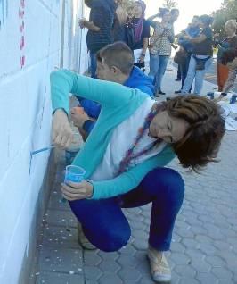 La comisionada participa en la pintada simbólica.