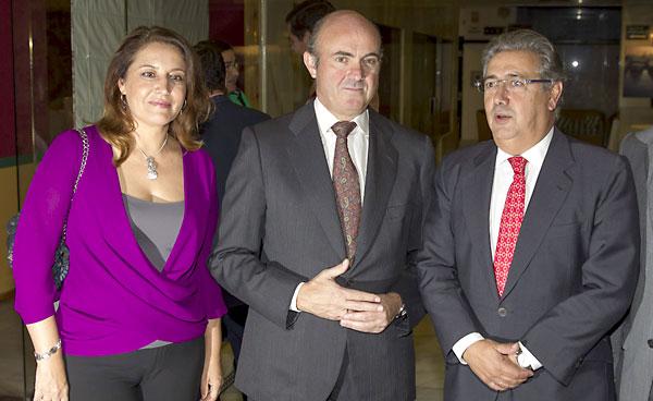 El ministro de Economía y Competitividad, Luis de Guindos, junto a la delegada del Gobierno en Andalucía, Carmen Crespo (i), y el presidente del PP andaluz y alcalde de Sevilla, Juan Ignacio Zoido (d), antes de pronunciar la conferencia inaugural del XXI curso de la Fundación Antares. / EFE