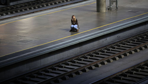 A woman sits on her suitcase as she waits for a train during a 24-hour nationwide train strike at Santa Just train station in Seville