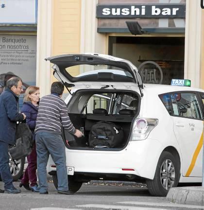 Un taxista de Sevilla introduce las maletas de unos clientes en su vehículo en una imagen tomada ayer. / J. M. PAISANO (ATESE)