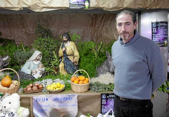 El representante vecinal y comercial de Los Remedios, Luis Juan Martín Godoy, ante el belén solidario instalado en el mercado del barrio. Foto: J.M. Espino (Atese)