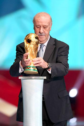 El entrenador de la selección española de fútbol, Vicente del Bosque, entrega la Copa del Mundo  durante el sorteo. / EFE