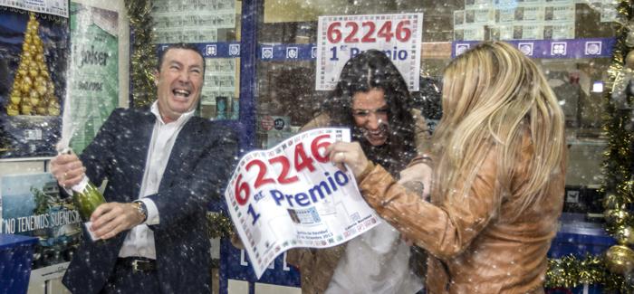 Juan Ignacio Jiménez, dueño de la administración de lotería de la localidad sevillana de San Lucar la Mayor descorcha una botella de champán. / EFE