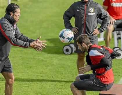 Baptistao devuelve el balón de cabeza a Simeone en un entrenamiento / Diego Souto