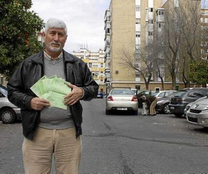 Pedro Salvador posa en la calle Abril con las decenas de multas puestas a los residentes. / Manu R.R. (Atese)