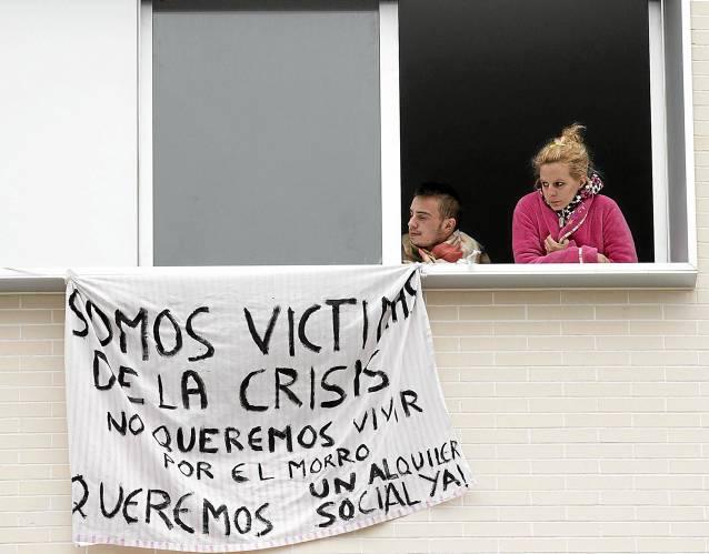 Dos de los ocupantes de las viviendas de Nuevo Amate cuelgan una pancarta en la que culpan a la crisis de su situación. / Pepo Herrera