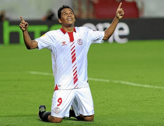 El delantero Carlos Bacca, celebra con su característico gesto uno de los goles marcados con la camiseta del Sevilla. (Marcamedia).