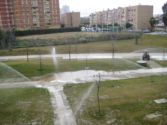El parque del Guadaíra, con charcos de la lluvia y el sistema de riego activo