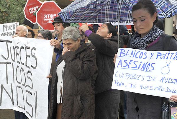 Afectados por amenaza de desahucios portan pancartas contra bancos, jueces y políticos, en Granada. / EFE