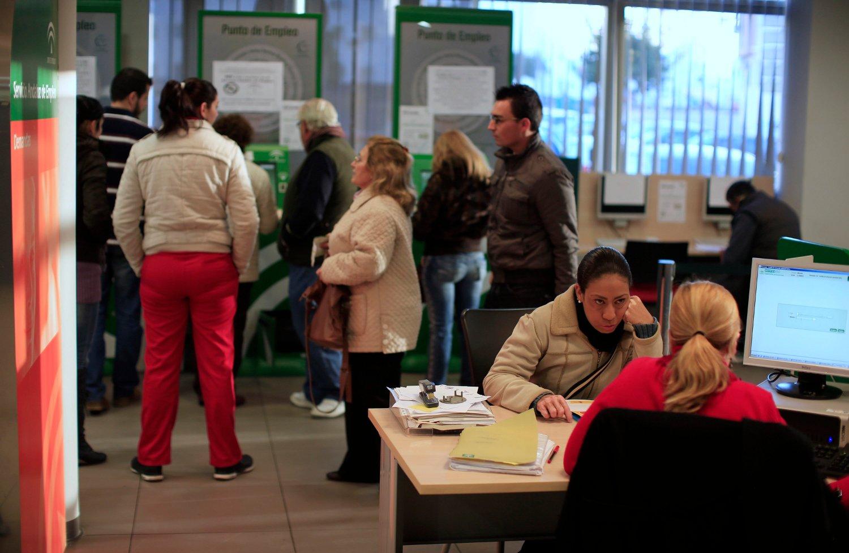 Una familia realizando una consulta en una oficina del SAE en la localidad de Dos Hermanas. / MARCELO DEL POZO (REUTERS)