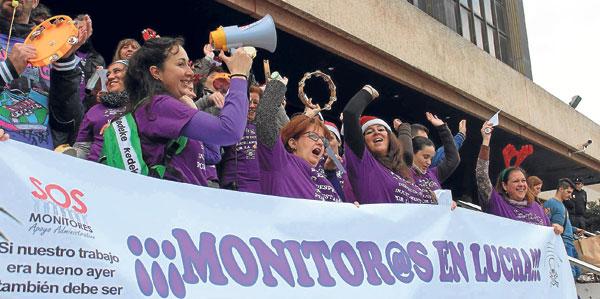 Decenas de monitores escolares, con camisetas moradas, protestaron ayer por la supresión de sus puestos de trabajo.