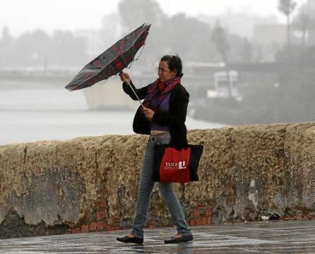 Una mujer lucha contra el viento y contra su paraguas a la vera del río, en uno de esos días imposibles de Sevilla. / Javier Díaz