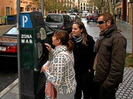 Usuarios de la zona azul pagando en un parquímetro del barrio del Arenal. / Antonio Acedo