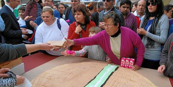 Vecinos de Utrera acudieron ayer a la plaza del Altozano para degustar el mostachón gigante elaborado por la asociación de confiteros de la localidad.