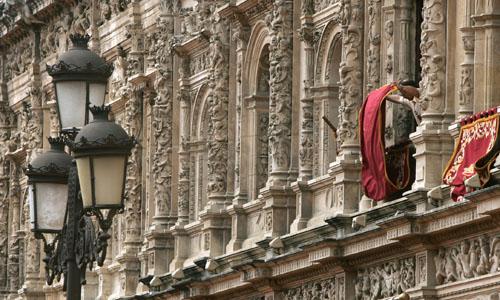 Un empleado del Ayuntamiento de Sevilla engalana las ventanas del consistorio. EFE