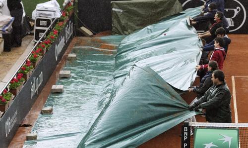 Operarios cubren la pista tras suspenderse temporalmente el primer partido de individuales de Copa Federación de Tenis.