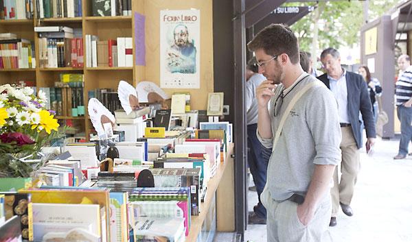 Un joven observa los libros de un stand en la última edición de la Feria del Libro de Sevilla. / J.M.Paisano (Atese)