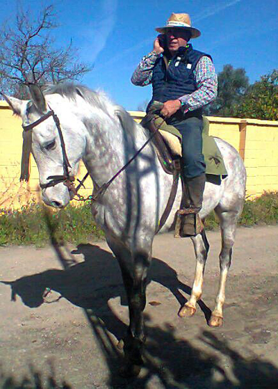 Emilio Gómez habla por teléfono montado en su caballo. / M.R.